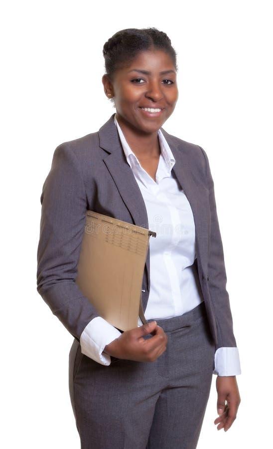 Mujer de negocios africana de risa con el fichero imagen de archivo