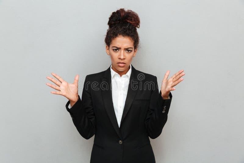 Mujer de negocios africana joven confusa que se coloca sobre la pared gris fotos de archivo