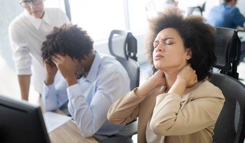 Mujer de negocios africana joven que tiene la tensi?n y dolor de cabeza en la oficina fotografía de archivo