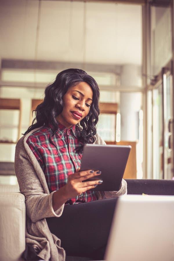 Mujer de negocios africana joven que trabaja en la tableta digital foto de archivo libre de regalías
