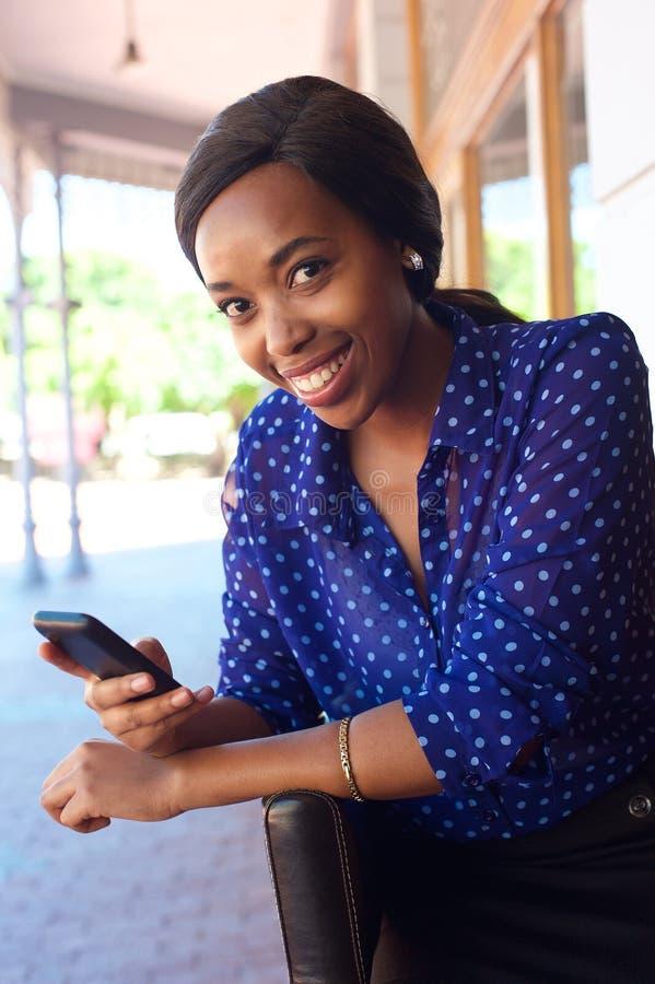Mujer de negocios africana sonriente con el teléfono celular imagenes de archivo