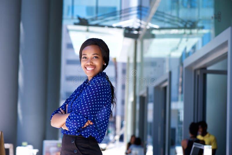 Mujer de negocios africana sonriente con los brazos cruzados foto de archivo