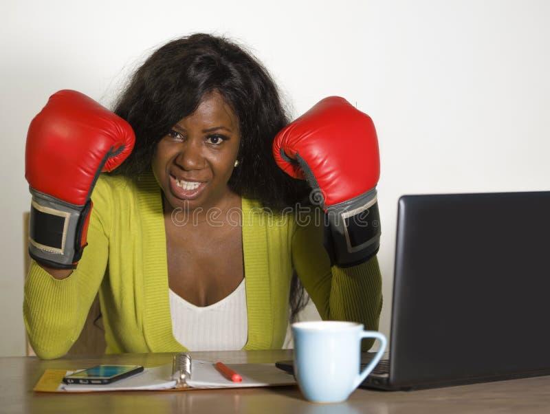 Mujer de negocios afroamericana furiosa y enojada joven en los guantes de boxeo subrayados por luchas del trabajo y de la negocia imágenes de archivo libres de regalías