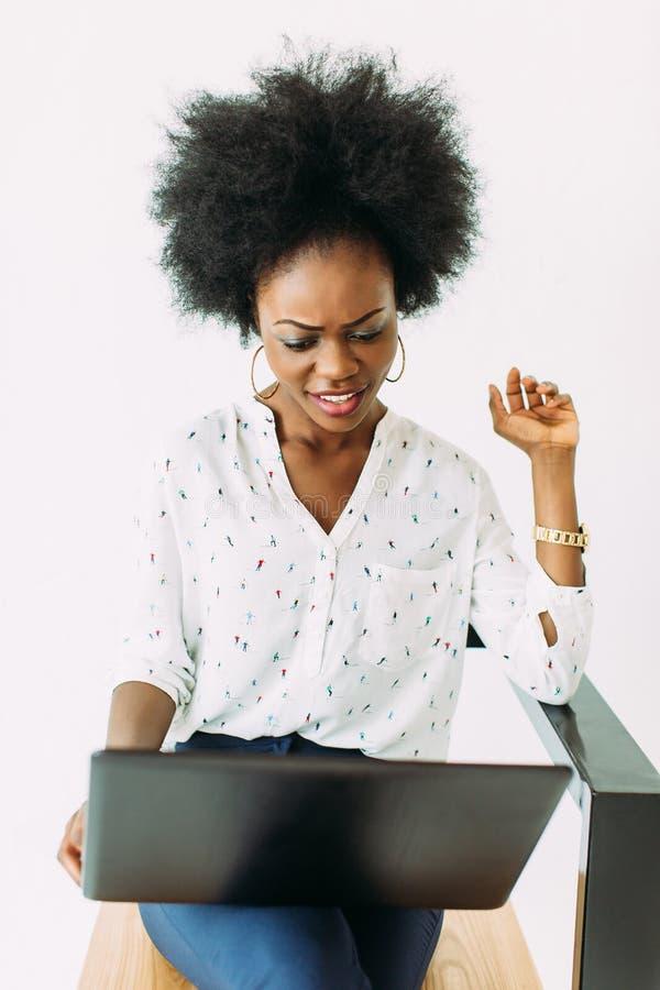Mujer de negocios afroamericana joven alegre concentrada y confundida, usando el ordenador portátil, aislado en blanco foto de archivo libre de regalías