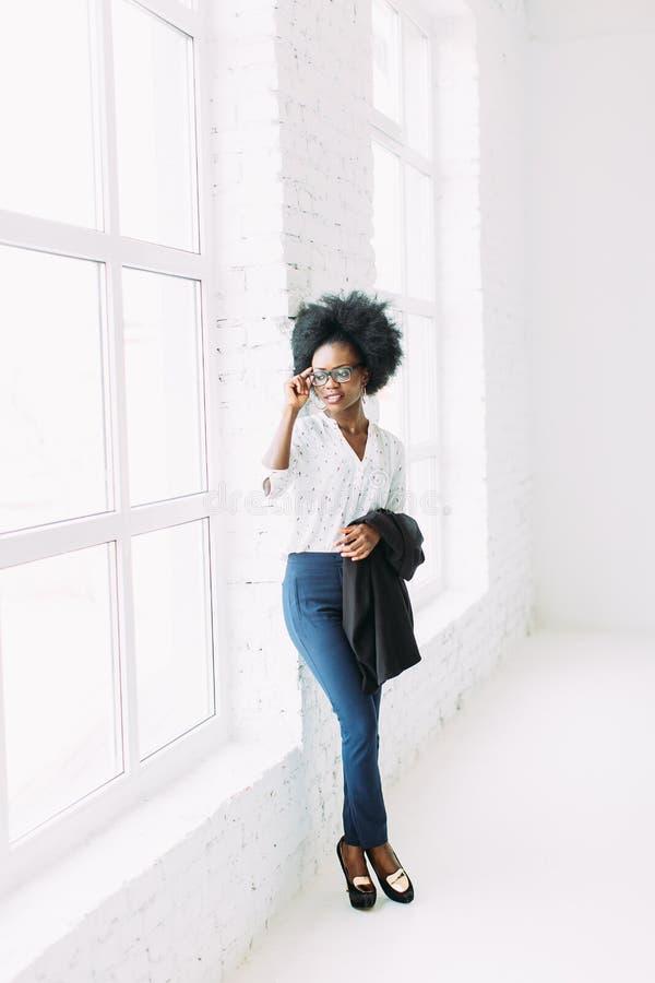 Mujer de negocios afroamericana joven en los vidrios, colocándose cerca de la ventana grande y sosteniendo la chaqueta fotografía de archivo
