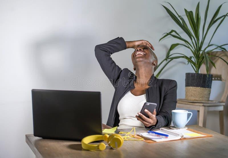Mujer de negocios afroamericana negra acertada que trabaja en inclinarse alegre sonriente de la oficina moderna relajado en silla fotos de archivo