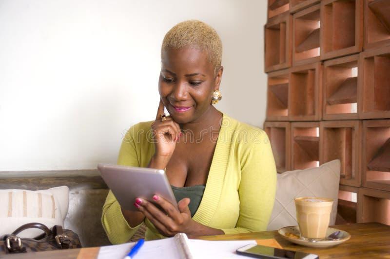 Mujer de negocios afroamericana negra elegante y hermosa joven que trabaja en línea con el cojín digital de la tableta en la cafe imagenes de archivo