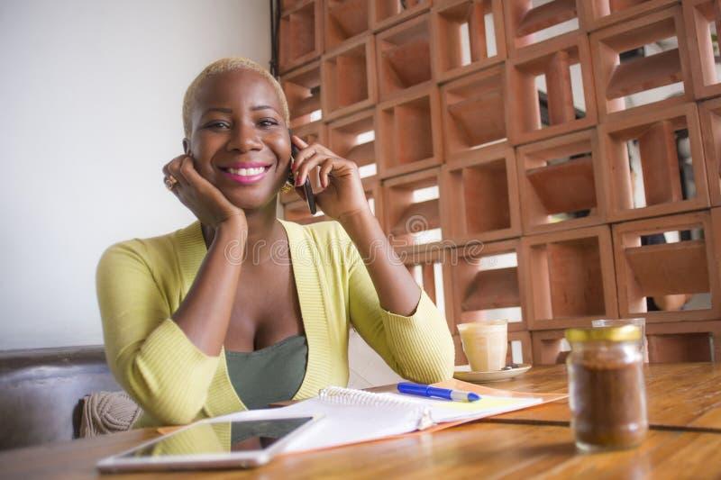 Mujer de negocios afroamericana negra elegante y hermosa joven que trabaja en línea con el teléfono móvil en la sonrisa de la caf imagen de archivo