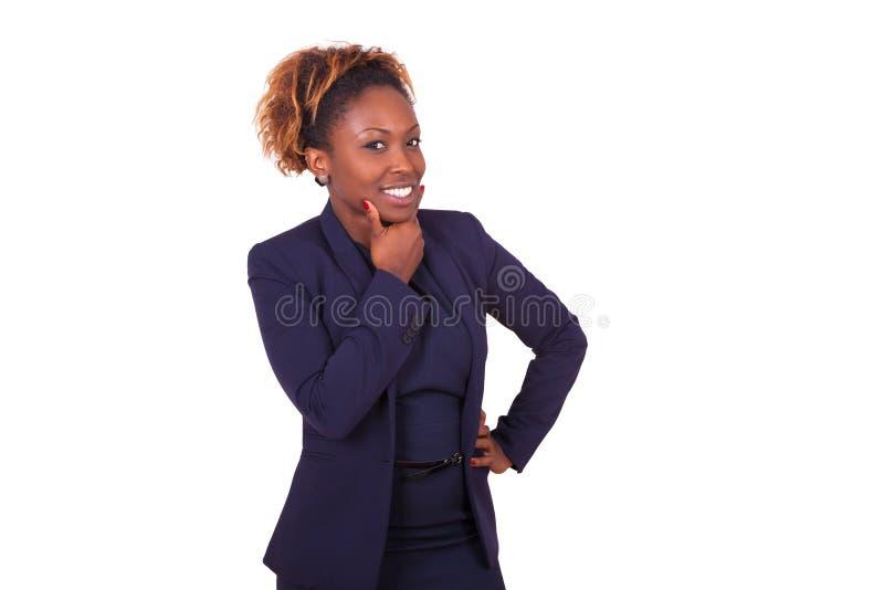 Mujer de negocios afroamericana pensativa aislada en los vagos blancos foto de archivo