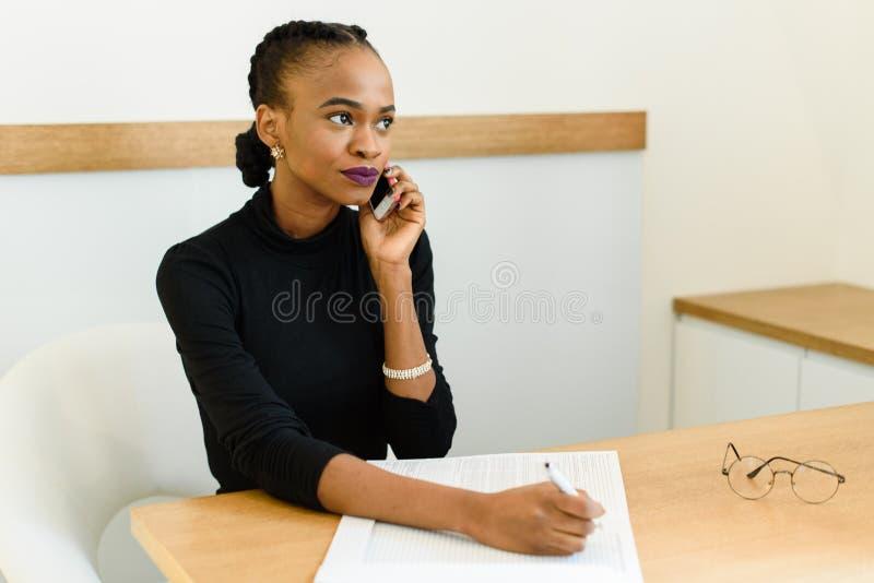 Mujer de negocios americana africana o negra joven confiada seria en el teléfono que mira lejos con la libreta en oficina imágenes de archivo libres de regalías