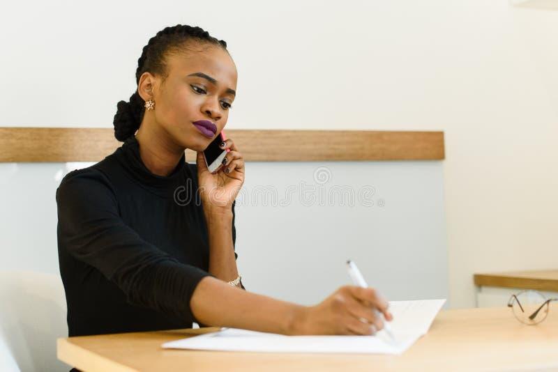 Mujer de negocios americana africana o negra joven confiada seria en el teléfono que toma notas en oficina imágenes de archivo libres de regalías