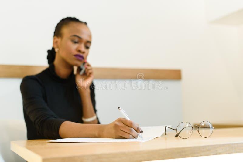 Mujer de negocios americana africana o negra joven confiada seria en el teléfono que toma notas en oficina imagen de archivo
