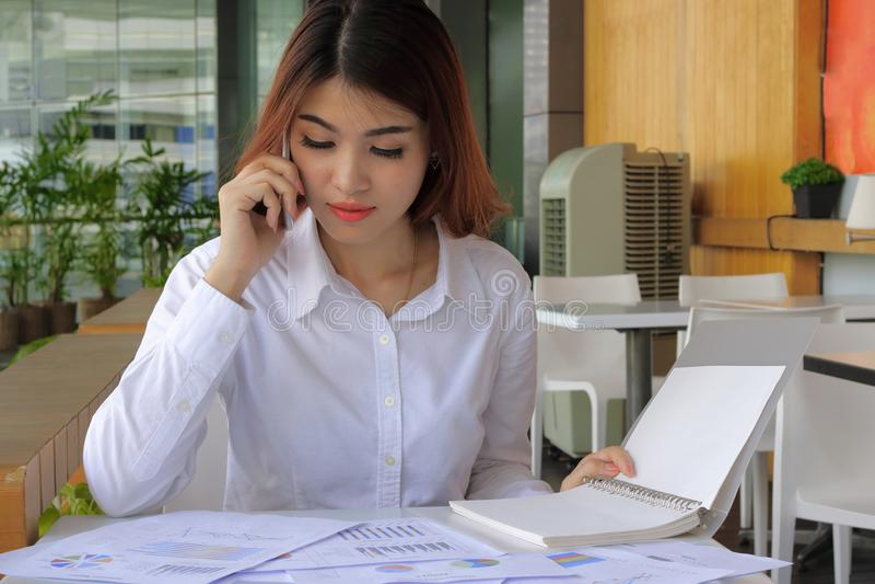Mujer de negocios asiática atractiva joven que trabaja con el teléfono móvil, carta en oficina imagen de archivo
