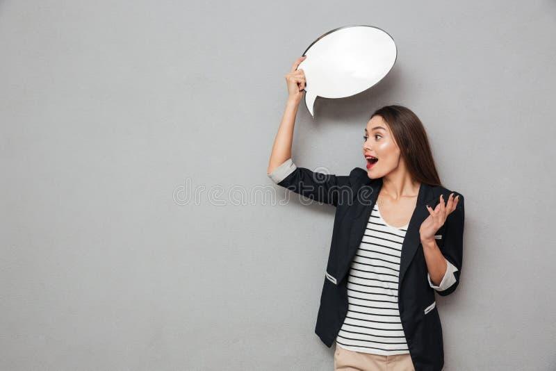 Mujer de negocios asiática chocada que lleva a cabo la burbuja en blanco del discurso de arriba imagen de archivo