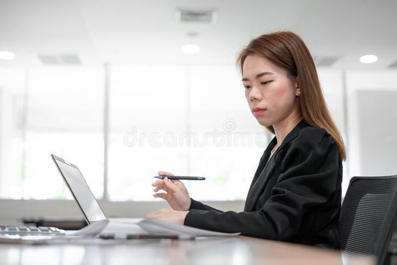 Mujer de negocios asiática del contable que trabaja en el escritorio y que mira el ordenador portátil en fondo interior de la ofi imagen de archivo
