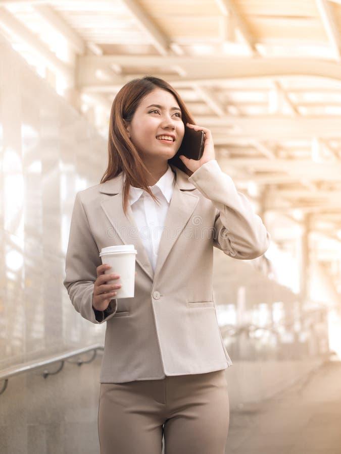 Mujer de negocios asiática elegante en un traje con el teléfono móvil y el holdi foto de archivo