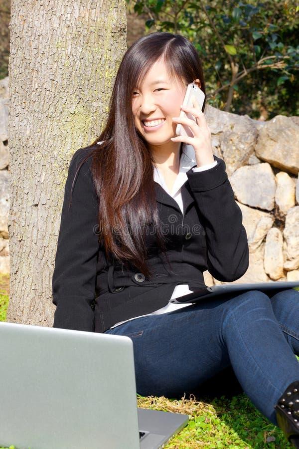 Mujer de negocios asiática en el parque que trabaja con PC y el teléfono fotos de archivo