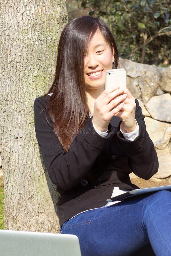 Mujer de negocios asiática en mensaje que manda un SMS del parque con el teléfono foto de archivo