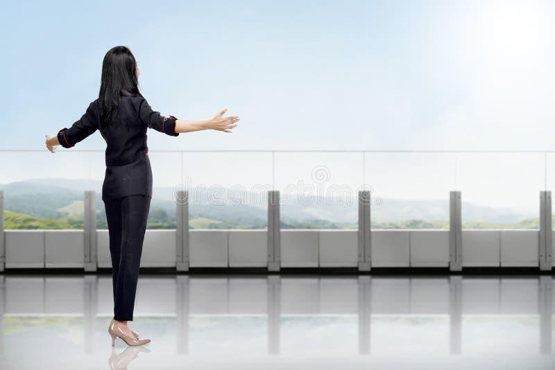 Mujer de negocios asiática feliz que disfruta de la opinión verde del paisaje imagenes de archivo
