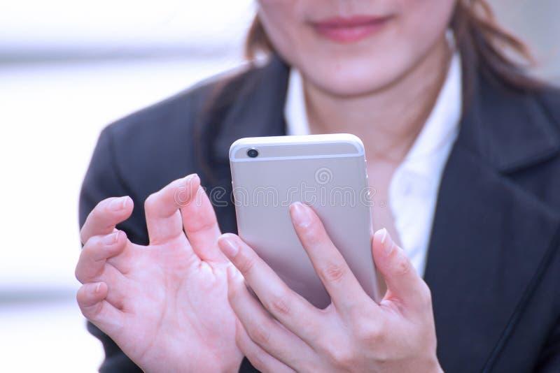 Mujer de negocios asiática feliz y sonrisa para utilizar el smartphone, negocio fotografía de archivo