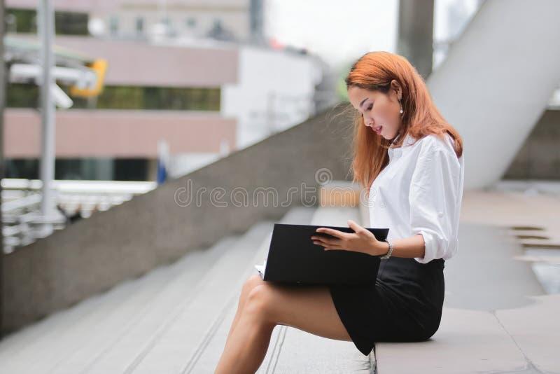 Mujer de negocios asiática joven atractiva que mira ficheros de documento en manos al aire libre imagen de archivo