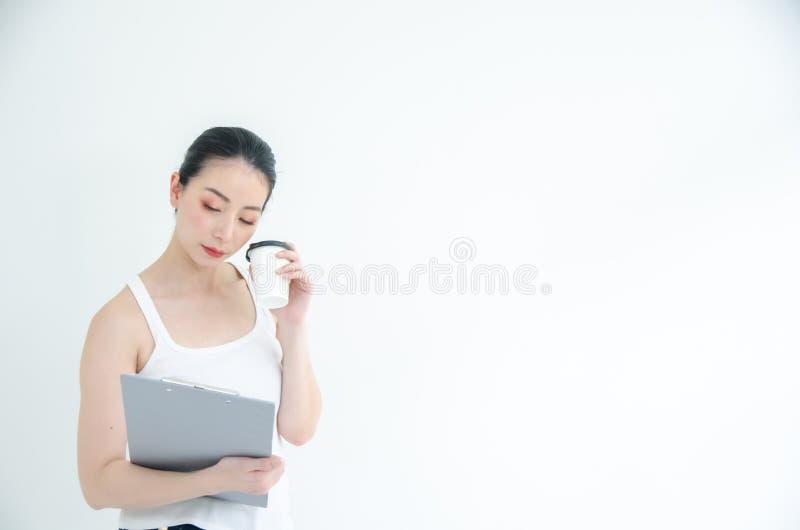 Mujer de negocios asiática joven bonita que sostiene una taza de ficheros del café y de documento Retrato aislado del estudio en  imágenes de archivo libres de regalías