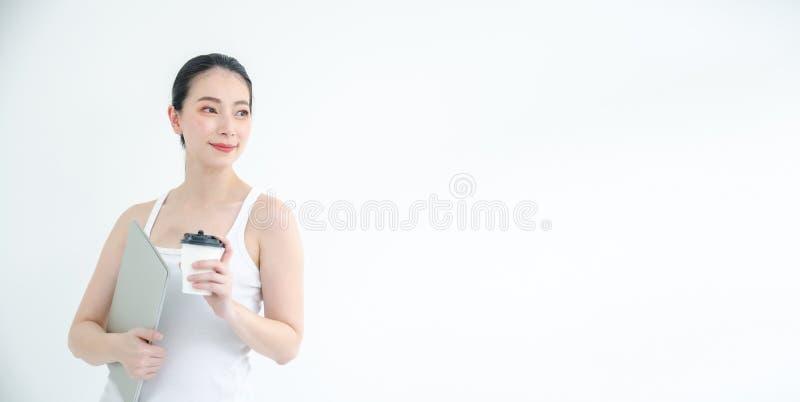 Mujer de negocios asiática joven bonita que sostiene una taza de ficheros del café y de documento Retrato aislado del estudio en  imagenes de archivo