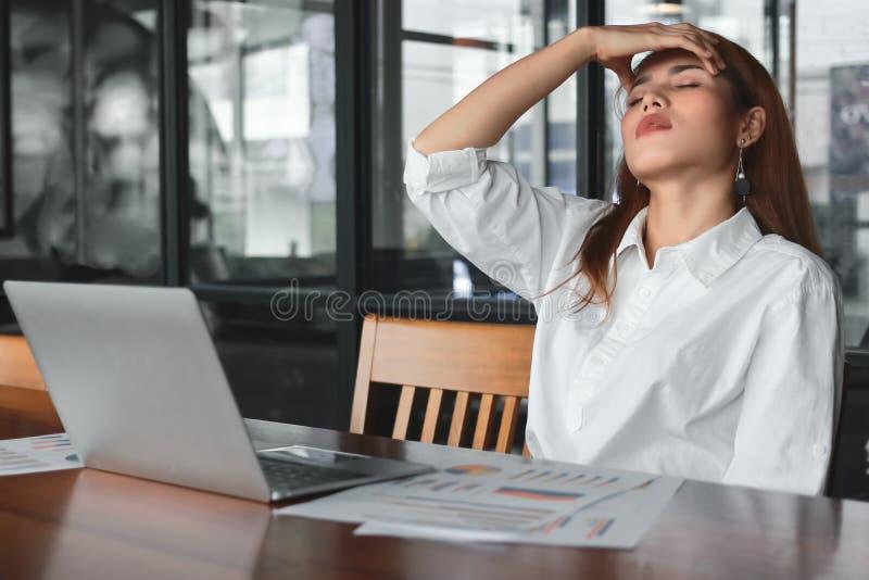 Mujer de negocios asiática joven con exceso de trabajo cansada que sufre de la depresión severa en lugar de trabajo fotos de archivo libres de regalías