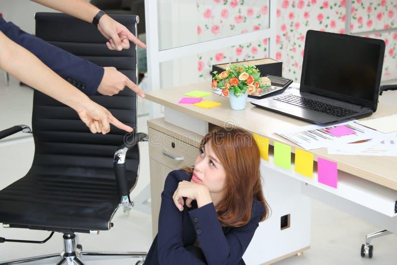 Mujer de negocios asiática joven del trastorno ansioso con los fingeres que señala en ella en el lugar de trabajo de la oficina imágenes de archivo libres de regalías
