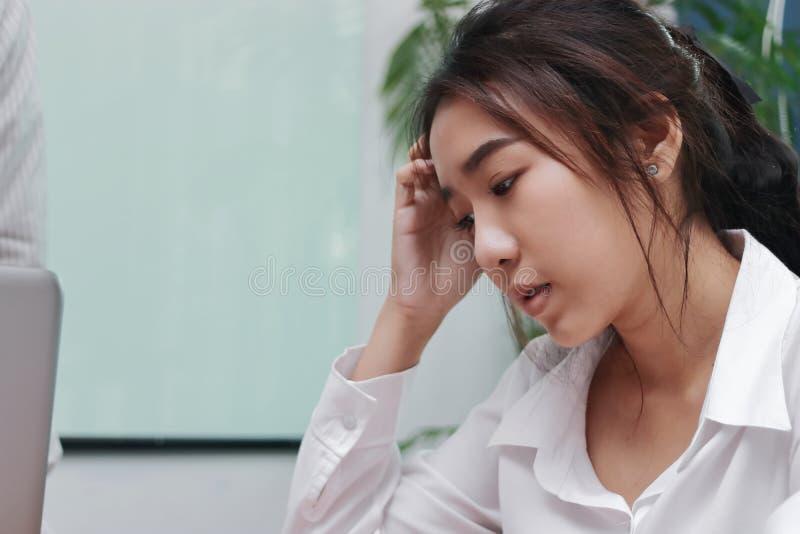 Mujer de negocios asiática joven infeliz que mira abajo en oficina fotos de archivo