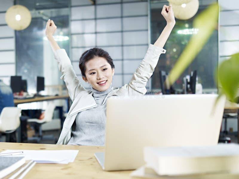 Mujer de negocios asiática joven que celebra en oficina fotos de archivo libres de regalías