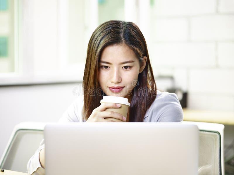 Mujer de negocios asiática joven que mira el ordenador portátil en oficina fotos de archivo libres de regalías