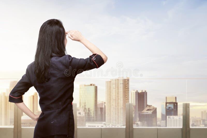 Mujer de negocios asiática joven que mira paisaje urbano fotos de archivo libres de regalías