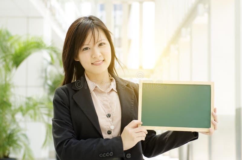 Mujer de negocios asiática joven que muestra al tablero en blanco fotografía de archivo libre de regalías