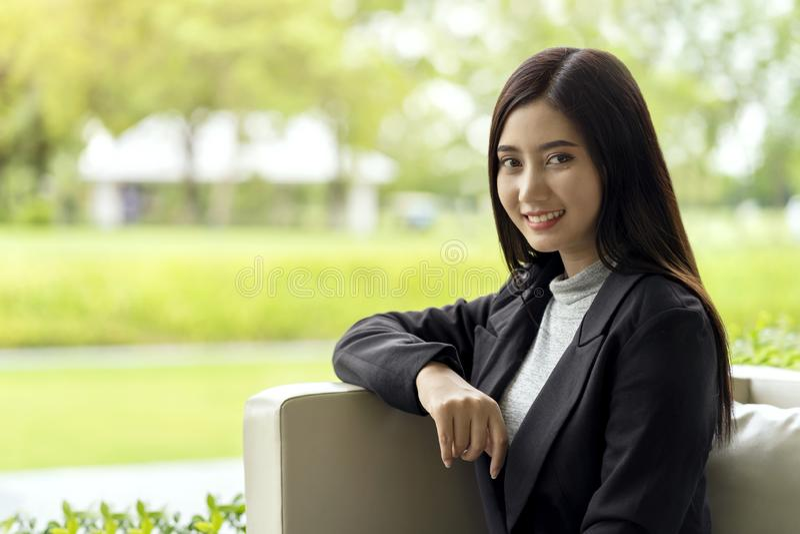 Mujer de negocios asiática joven que parece feliz y sonrisa, sentándose en el sofá, fondo verde del parque foto de archivo libre de regalías