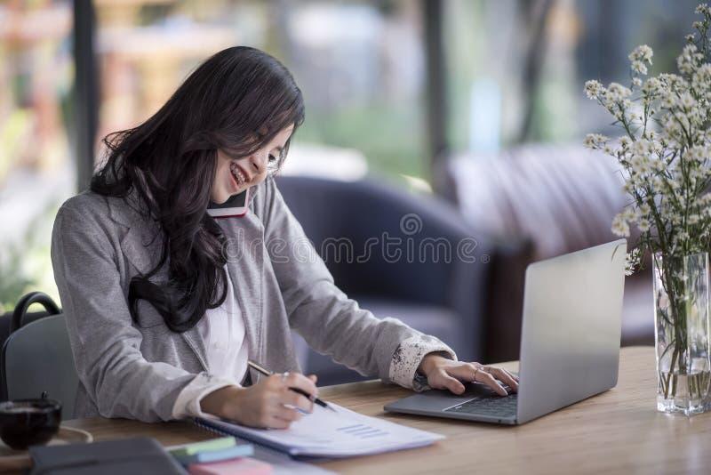 mujer de negocios asiática joven que trabaja detrás de un escritorio con charla del ordenador portátil fotografía de archivo libre de regalías