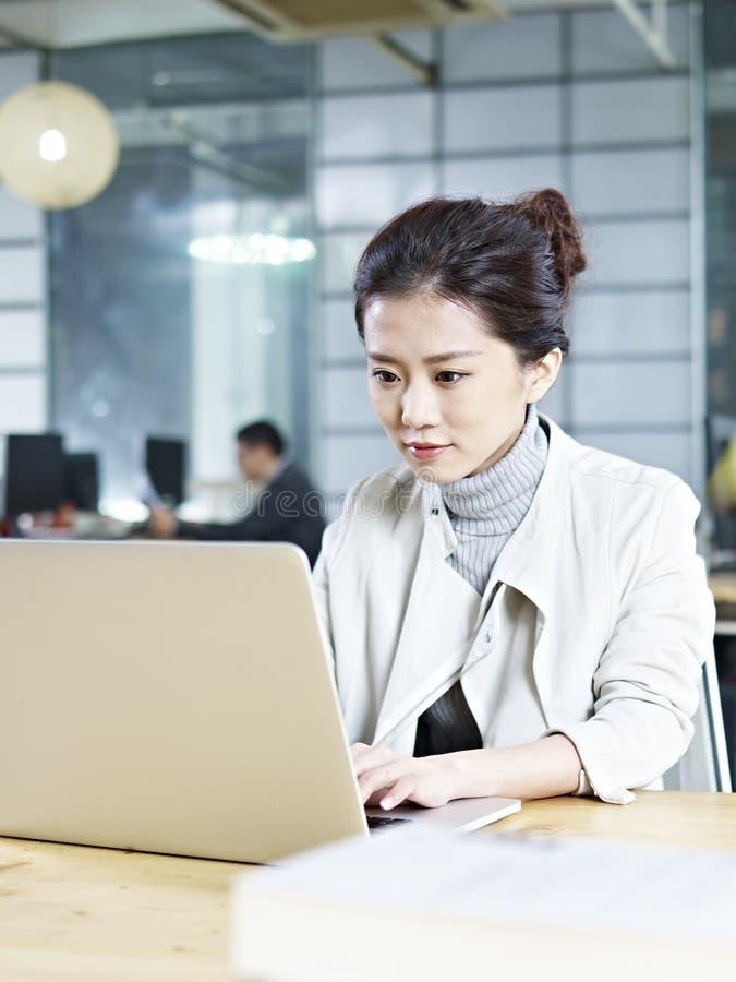 Mujer de negocios asiática joven que trabaja en oficina foto de archivo