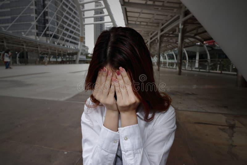 Mujer de negocios asiática joven subrayada ansiosa que sufre de la depresión y del grito severos imagenes de archivo