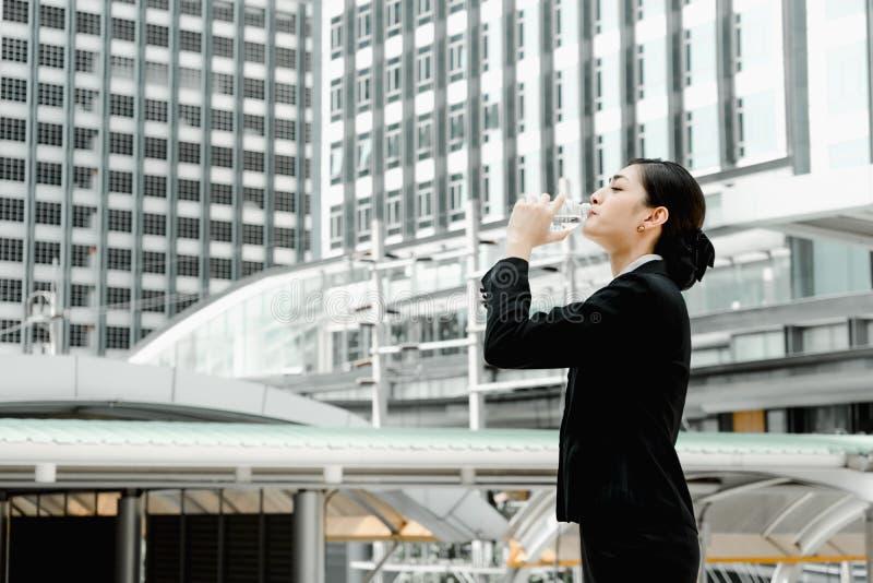 Mujer de negocios asiática que coloca y que bebe el agua mineral pura de la botella plástica con el fondo del edificio imagenes de archivo