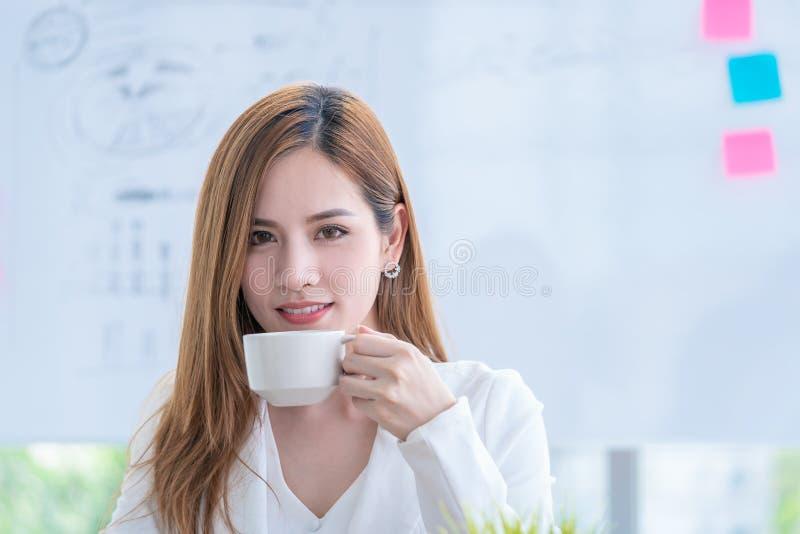 Mujer de negocios asiática que comprueba el informe mientras que bebe el café foto de archivo libre de regalías