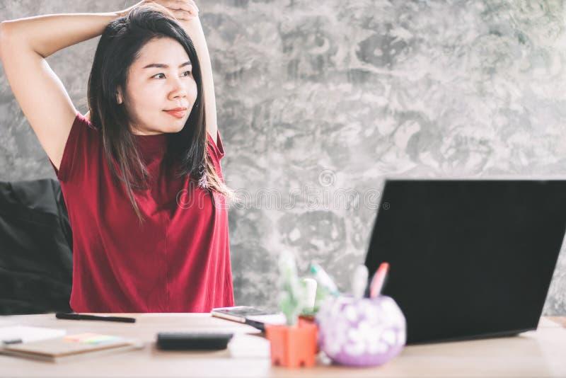 Mujer de negocios asiática que estira el brazo para relajar el músculo de los omóplatos que se sientan en la oficina imagenes de archivo