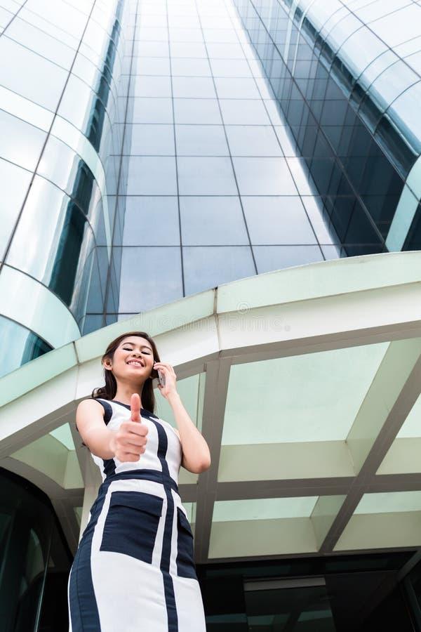 Mujer de negocios asiática que llama por teléfono afuera con el teléfono fotografía de archivo