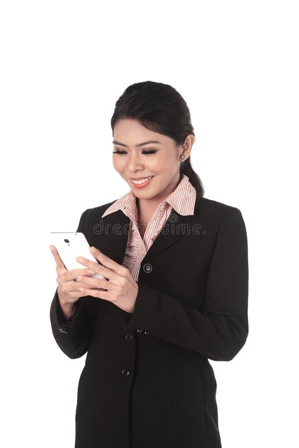 Mujer de negocios asiática que manda un SMS en su teléfono móvil imagen de archivo libre de regalías