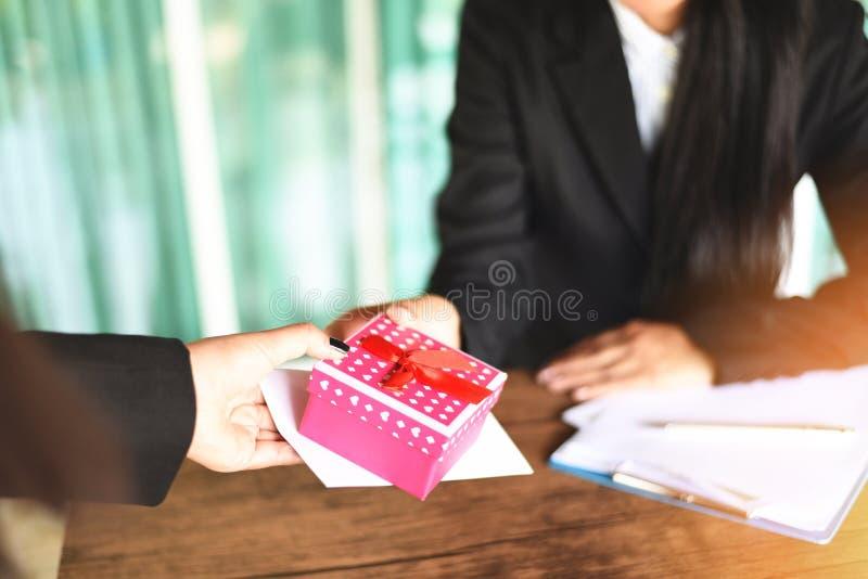 Mujer de negocios asiática que recibe el dinero de la prima del sueldo y la caja de regalo del jefe o del encargado en el concept fotos de archivo libres de regalías