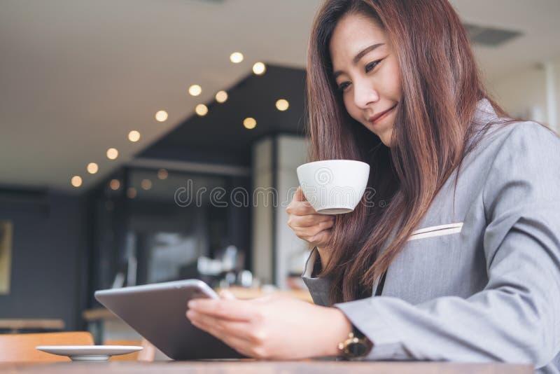 Mujer de negocios asiática que sostiene y que mira la PC de la tableta mientras que bebe el café en café moderno imágenes de archivo libres de regalías