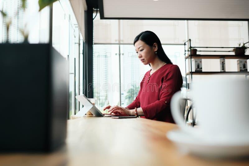 Mujer de negocios asiática que trabaja en barra fuera de la oficina fotos de archivo libres de regalías