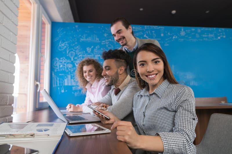 Mujer de negocios asiática que usa al grupo de los empresarios del ordenador portátil en equipo diverso de centro de los compañer fotografía de archivo