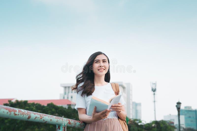 Mujer de negocios asiática que viaja, puente de la verja que hace una pausa, libro de lectura en fondo de la ciudad foto de archivo libre de regalías
