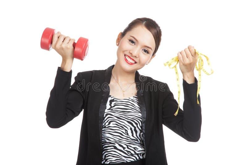 Mujer de negocios asiática sana con pesas de gimnasia y cinta métrica fotos de archivo