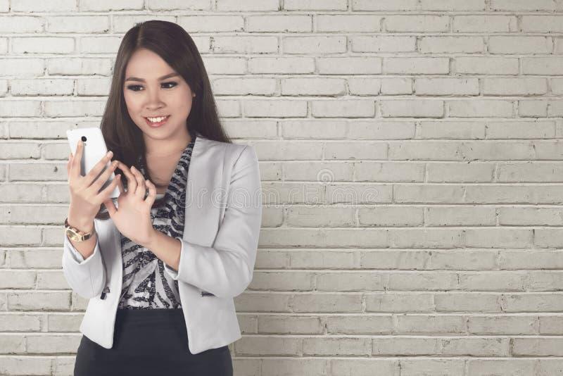 Mujer de negocios asiática sonriente que mecanografía mientras que sostiene el ordenador portátil foto de archivo libre de regalías